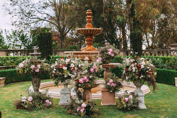 Wedding ceremony outdoors fountain at altar pink flowers in vintage antique style vases urns