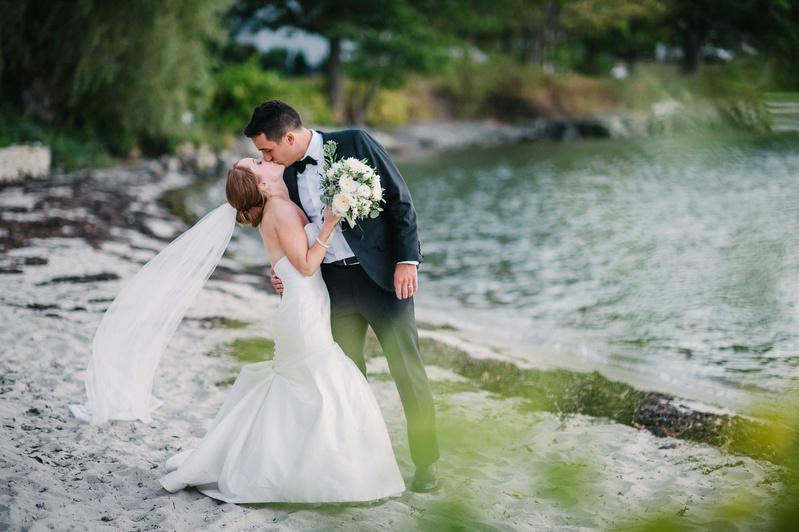couple kissing beach maine cape elizabeth sand green color palette wedding rivini dress