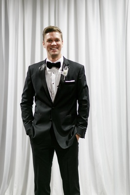 groom in classic black tuxedo, hands in pockets, white feather boutonniere, white drapery