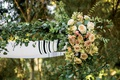 close up of tallit chuppah jewish wedding ceremony outdoor greenery pink white peach roses flowers