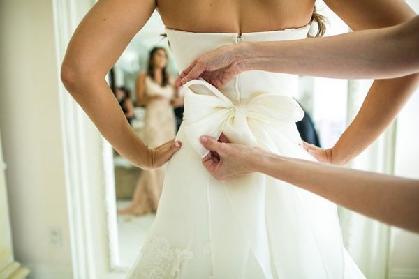 wedding dress in bridal suite strapless gown with big bow in back bridesmaid mother helping