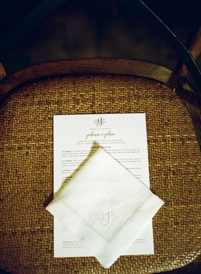 Ceremony program and handkerchief on guest seat at wedding ceremony with custom monogram