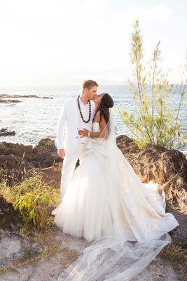 Joshua Faulkner in white suit with kukui nut shell lei and Chudney Ross in Lazaro wedding dress gold
