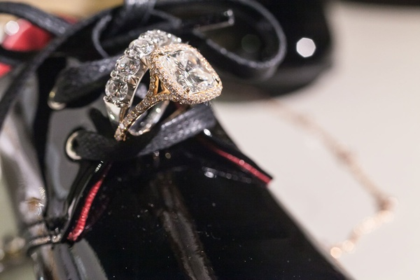 Same sex wedding jewelry eternity band and halo engagement ring on patent leather shoe