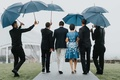 wedding guests walking to tented ceremony umbrellas held by staff mother of bride in blue white dres