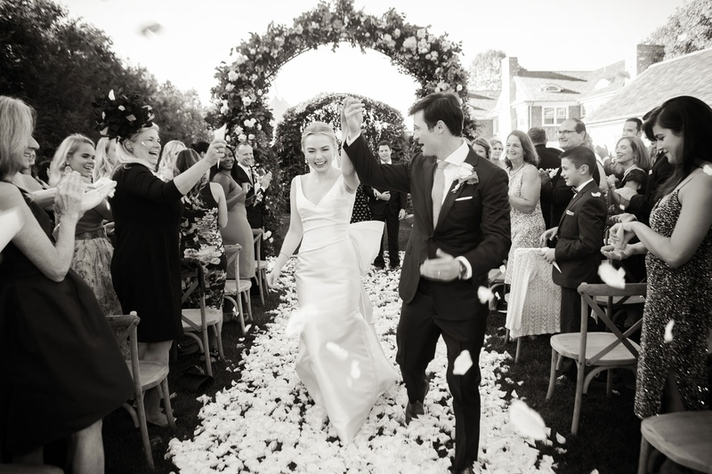 black and white photo of bride in classic wedding dress with groom flower petal toss recessional