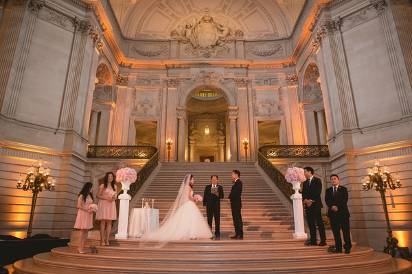 Bride in a strapless Kenneth Pool dress with tulle skirt, veil, groom in black tux at wedding