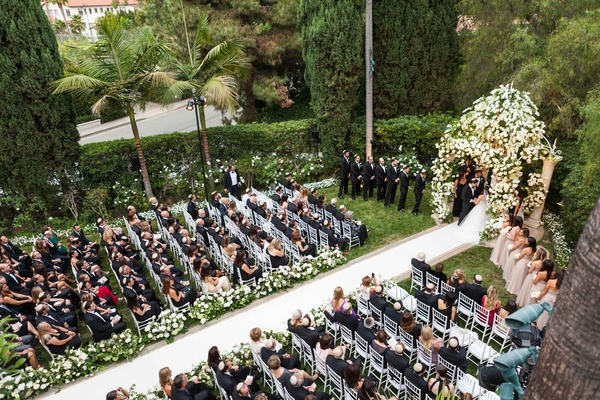 Guests sitting down for outdoor Beverly Hills Hotel wedding ceremony aisle runner chuppah palm trees