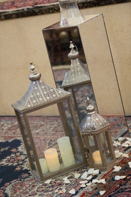Moroccan lantern on Persian rug with rose petals and candles next to mirror riser at church ceremony