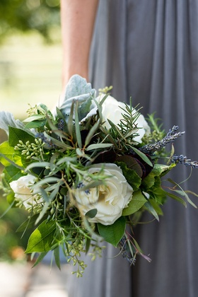 Bridesmaid in grey dress holds green and white bouquet with dusty miller lamb's ear lavender