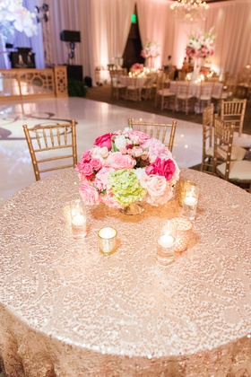 wedding reception table with sequin linen stitched in a pattern, pink florals