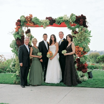 Bride and groom with both sets of parents under chuppah