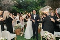 Bride in Monique Lhuillier and groom walking up aisle at Hotel Bel-Air sparklers waved by guests