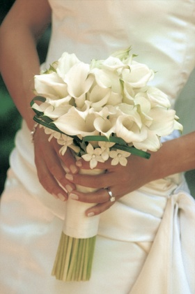 Bride holds bouquet with white flowers