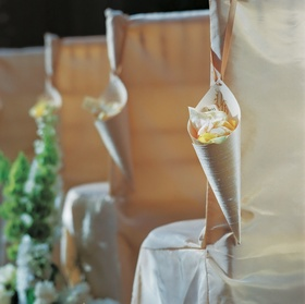 Paper cones filled with rose petals and hung from chairs for a wedding