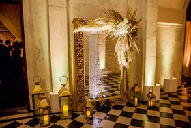 gold framed mirror seating chart with pampas grass on the corner, lanterns