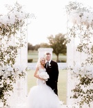 White gate to ceremony space wedding portrait greenery white flowers decor Dallas ceremony
