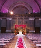Clear chiavari chairs at Weylin B. Seymour's venue with floral chuppah and flower petal aisle