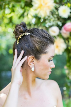bride with hair up in high bun gold laurel wreath headpiece large earrings manicure