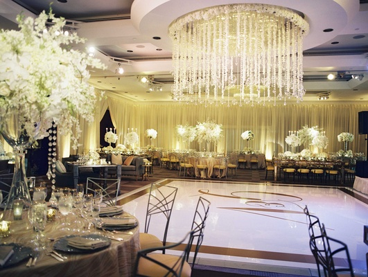 Ceiling flower and crystal arrangement over dance floor in ballroom reception monogram dance floor