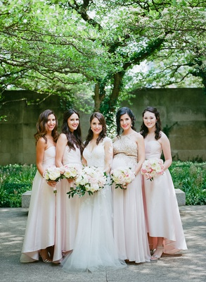 bride with bridesmaids in light pink high low dresses strapless pregnant bridesmaid different gown