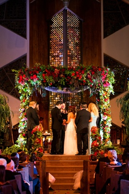 Bride and groom under chuppah with greenery and red flowers indoor Jewish temple wedding ceremony