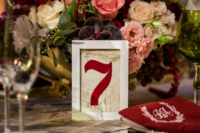 White frame with gold background and burgundy table number next to centerpiece with roses succulents