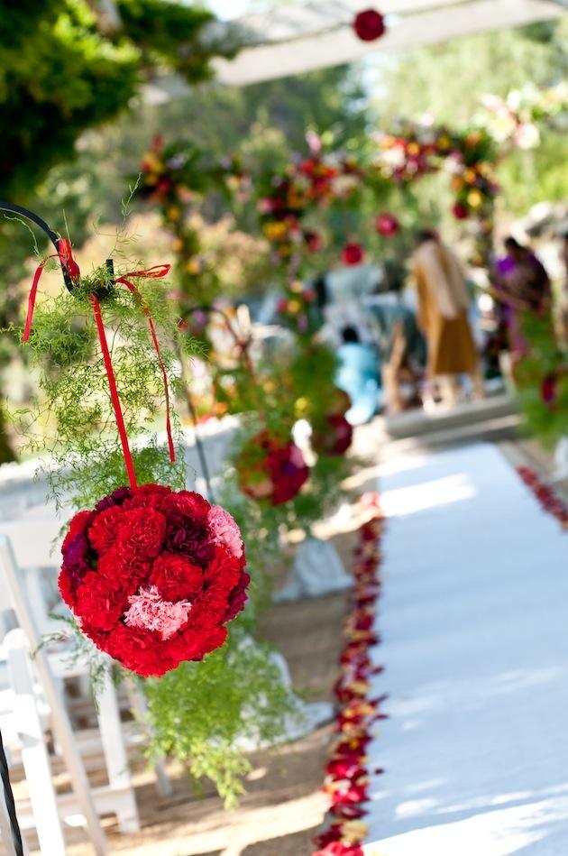Red carnation pomander balls line aisle runner
