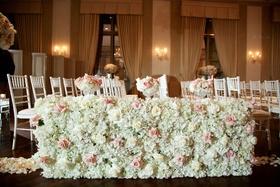 White hydrangea pink rose ivory rose flower wall along wood floor aisle ballroom wedding ceremony