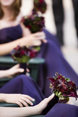 Bridesmaids in amethyst dresses holding nosegay