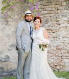 bride in high neck beaded wedding dress white pink bouquet groom in light grey suit fedora