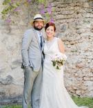 bride in high neck beaded wedding dress white pink bouquet groom in light grey suit fedora