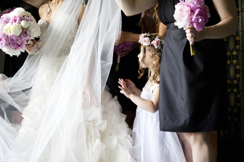Flower girl in white dress with thick straps and pink rose crown looks at bride in strapless Lazaro