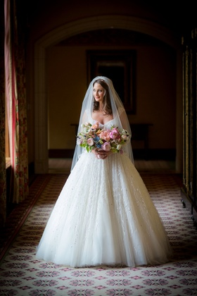Bride in Zuhair Murad wedding dress ball gown and veil with colorful pink blue bouquet