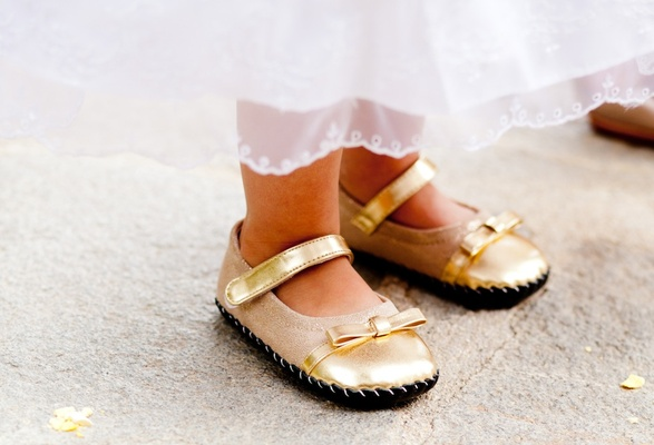 Moccasin-style gold shoes with ankle strap and bow