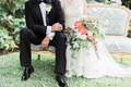 Groom in tuxedo and dress shoes with rustic boutonniere bride in Jinza Bridal Couture with bouquet