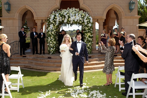Bride and groom walk up grass aisle at The Grand Del Mar