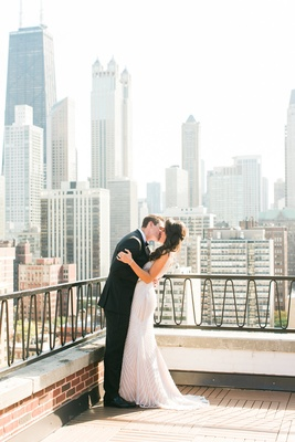 Bride and groom kiss on Chicago balcony with skyscrapers and skyline in background