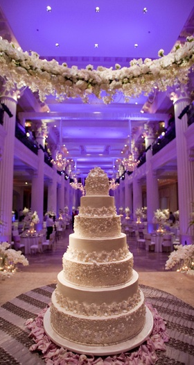 White wedding cake under garland of white flowers