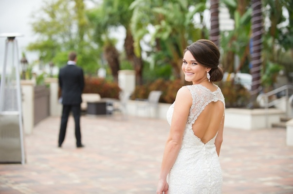 Bride wearing diamond earrings and lace wedding dress