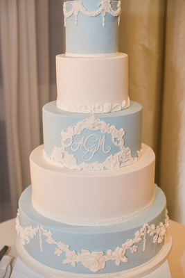five-tier wedding cake alternating in pale blue and white, molded floral accents, monogram