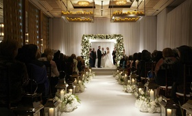 Bride and groom beneath flower chuppah in white ballroom