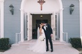 bride in romona keveza, groom in suit, newlyweds kiss in front of church