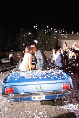 Bride and groom on top of vintage blue Mustang at wedding