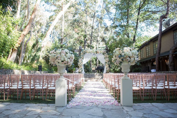 wedding ceremony outdoor venue stone aisle flower petals tall risers blush rose gold chairs