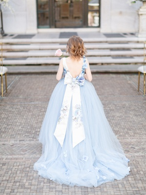 back of flower girl in blue tulle ball gown and large floral sash