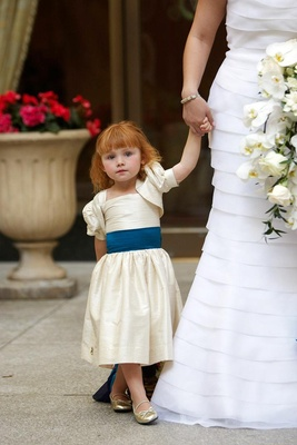 Redhead wearing ivory dress and gold shoes