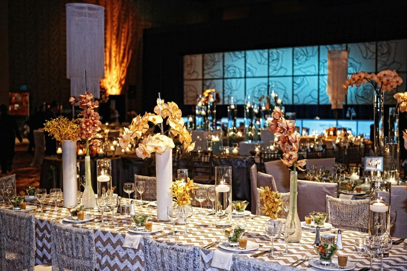 Wedding reception table lined with tall and low clear and milky vases with orchids