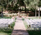 Outdoor wedding ceremony with stone aisle and white chairs lantern flowers alfresco grass lawn