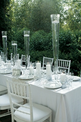 Wedding Reception Table With White Tablecloths Chairs And Tall Vases Floating Candles